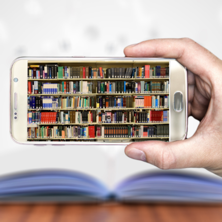 Personne qui tient un téléphone avec une bibliothèque de livres en photo.